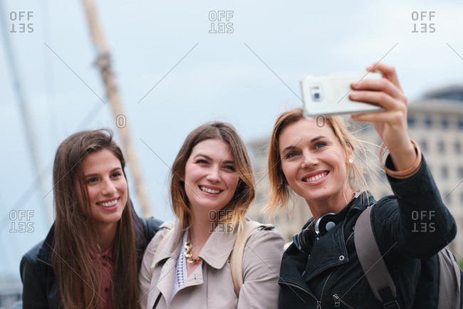 Travel friends taking selfie photo using smartphone camera in city group of women having fun sharing reunion on social media with mobile phone technology