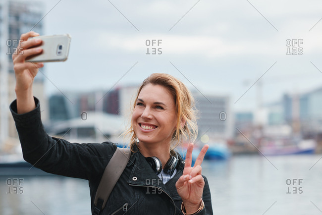 Beautiful travel woman taking selfie photo using smartphone camera in waterfront harbor making peace sight with hand sharing vacation holding mobile phone