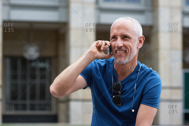 Mature man using smartphone having phone call talking on mobile phone  in city