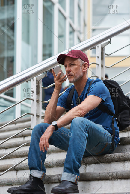 Travel man using smartphone having phone call talking on mobile phone sitting on stairs in city