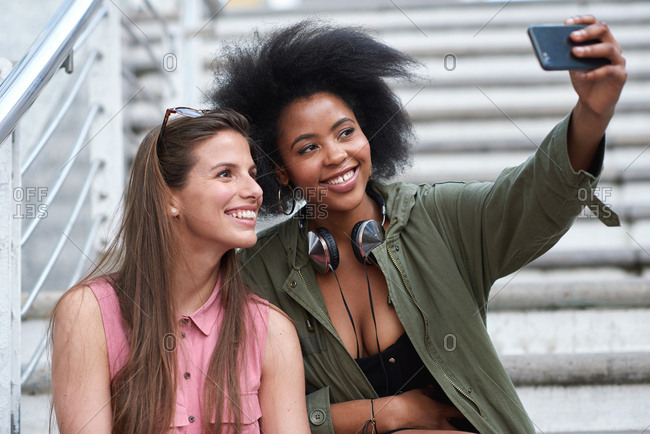 African american woman taking photo with friend using smartphone camera beautiful women sharing friendship on social media