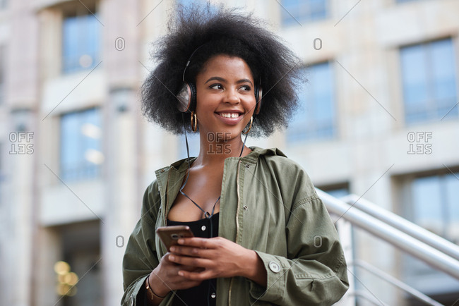 Young african american woman wearing headphones listening to music using smartphone in city
