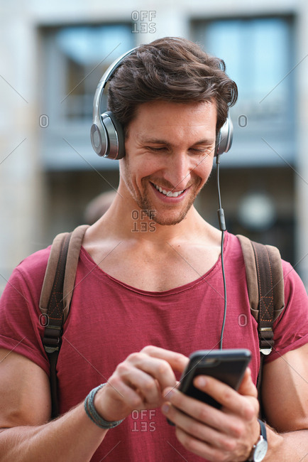 Attractive man using smartphone in city wearing headphones listening to music smiling happy enjoying mobile technology