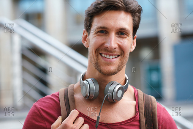 Portrait happy young man smiling confident feeling positive in city urban success testimonial