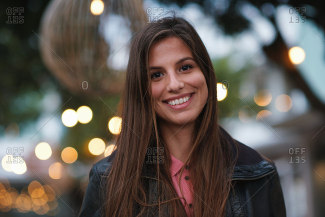 Portrait beautiful woman smiling happy in city evening with lights in background