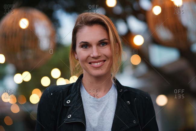 Portrait beautiful blonde woman smiling happy in city evening with lights in background