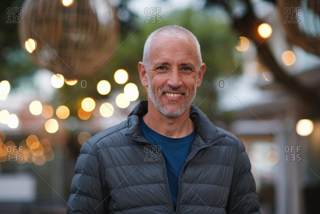 Portrait mature man smiling happy in city evening with lights in background