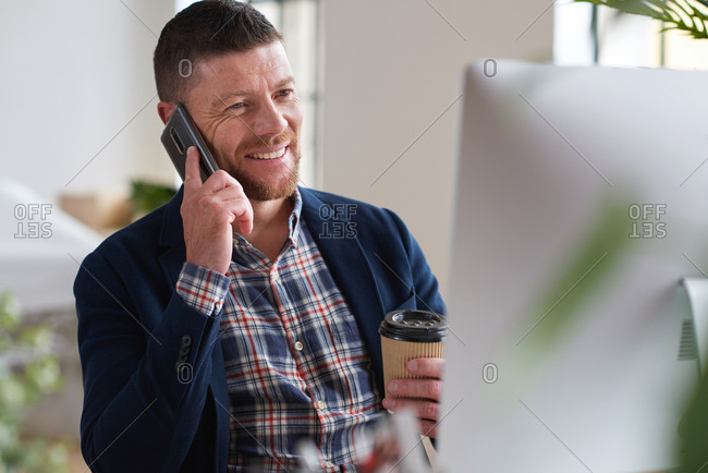 Businessman using smartphone talking with client on mobile phone call in office holding coffee