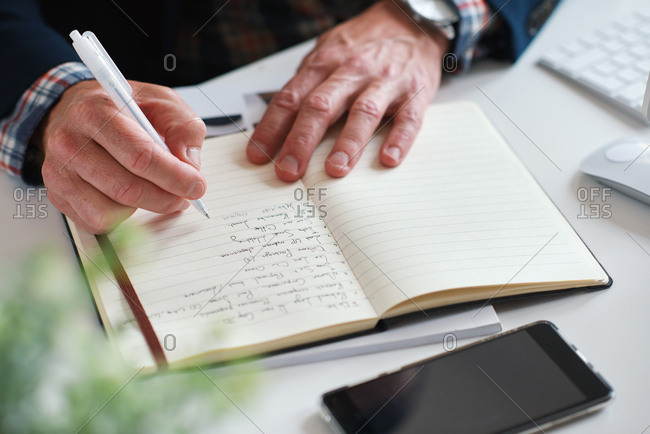 Businessman hands writing in notebook journal on desk list of goals in diary making notes