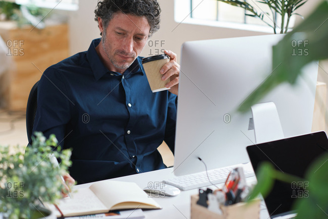 Businessman writing in notebook journal brainstorming ideas holding coffee sitting at desk in office
