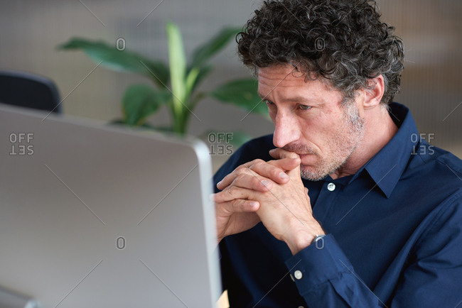 Mature businessman thinking using computer in office brainstorming male entrepreneur contemplating creative ideas planning strategy looking pensive