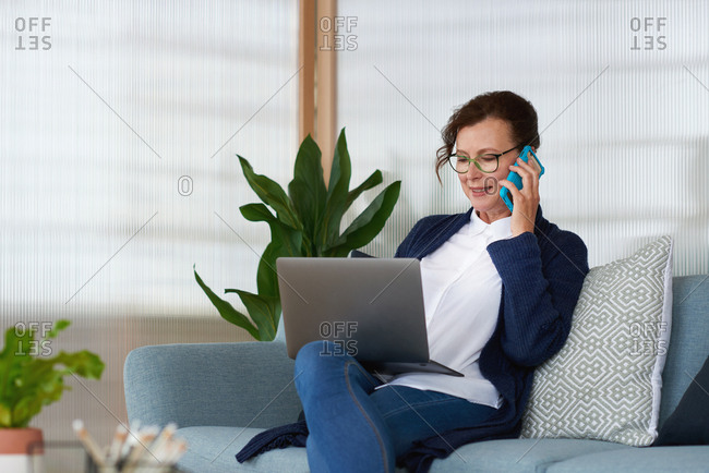 Mature business woman using laptop computer in office chatting to client on smartphone sitting on sofa in office