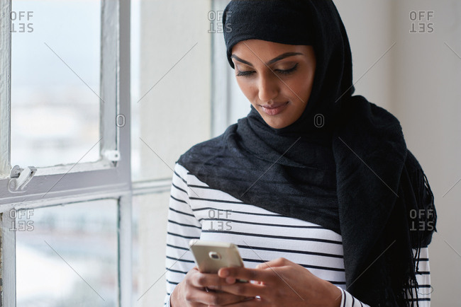 Muslim woman using smartphone texting on mobile phone browsing messages wearing hijab headscarf standing by window
