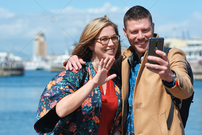 Happy couple taking photo using smartphone in harbor waterfront sharing vacation photographing holiday memories with mobile phone camera