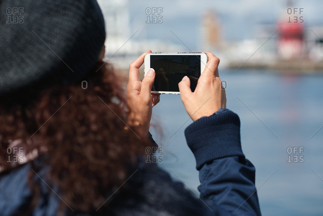 Travel woman taking photo using smartphone camera sharing vacation holding mobile phone wearing winter clothes