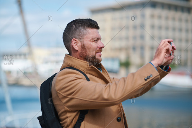 Man using smartphone taking photo of harbor with mobile phone camera tourist on vacation