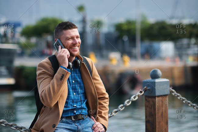 Businessman man using smartphone having phone call talking on mobile phone in waterfront harbor
