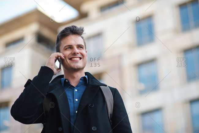 Businessman man using smartphone having phone call talking on mobile phone in city