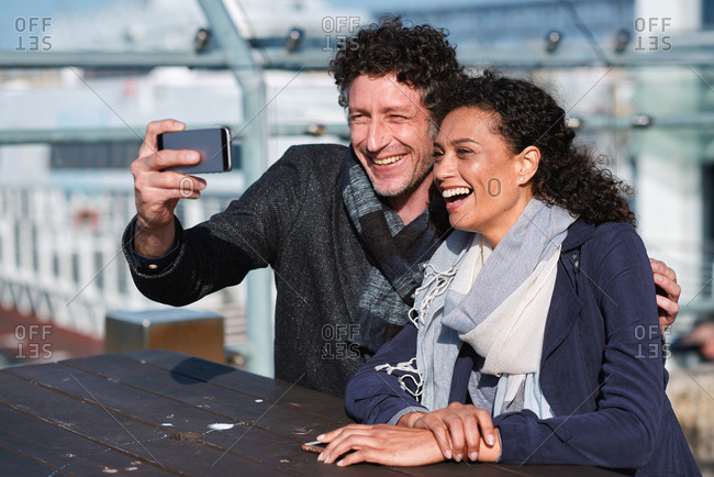Happy couple taking photo using smartphone in waterfront sharing vacation photographing holiday memories with mobile phone camera