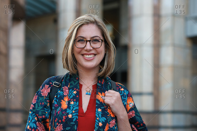 Portrait beautiful young woman smiling confident independent female in city wearing colorful clothes