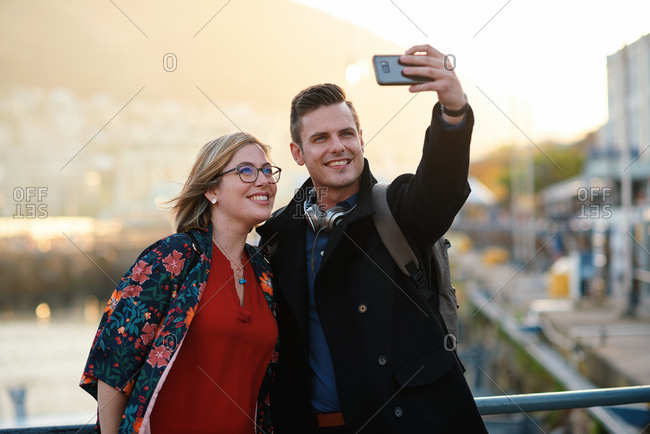 Young couple taking photo using smartphone in harbor waterfront sharing vacation photographing holiday memories with mobile phone camera