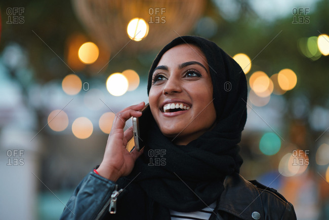 Portrait muslim woman using smartphone having phone call talking on mobile phone in city evening wearing hijab headscarf