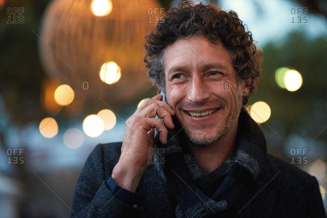 Mature man using smartphone having phone call talking on mobile phone city evening