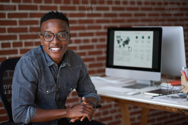 Portrait successful african american businessman smiling confident in office sitting at desk
