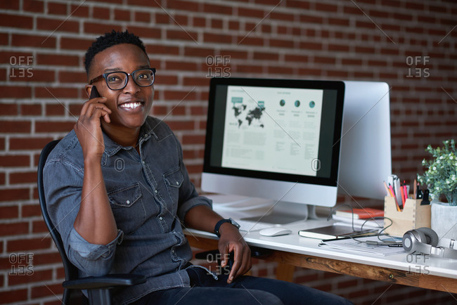 Portrait african american businessman using smartphone having conversation talking on mobile phone smiling happy in office sitting at desk