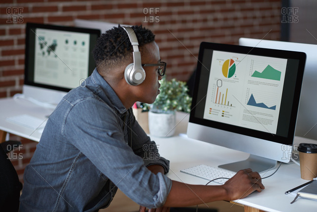 African american businessman using computer with financial graph data on screen wearing headphones listening to music in office