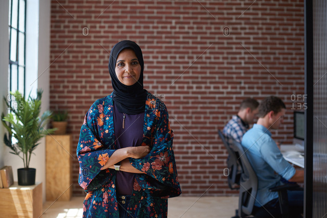 Successful muslim business woman smiling confident with arms crossed female manager in office