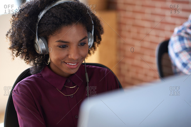 Beautiful african american woman using computer wearing headphones listening to music in office