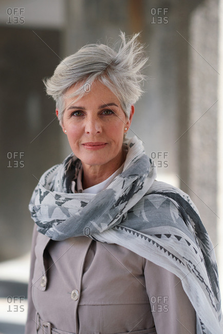Portrait mature business woman smiling confident successful female in urban city wearing scarf success testimonial