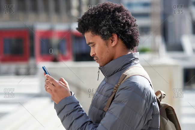 Man using smartphone in city texting on mobile phone browsing online