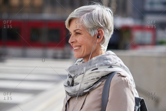 Portrait mature business woman wearing earphones listening to music in city