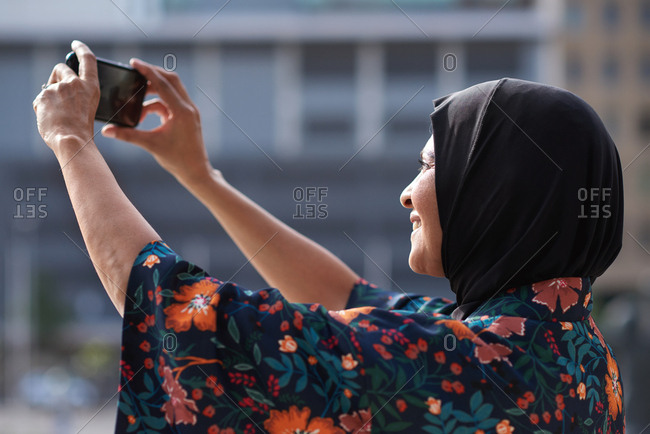 Muslim woman taking photo using smartphone in city tourist photographing urban travel with mobile phone camera wearing hijab headscarf