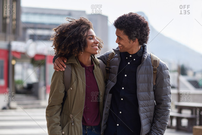 Happy multiracial couple hug showing affection walking in city