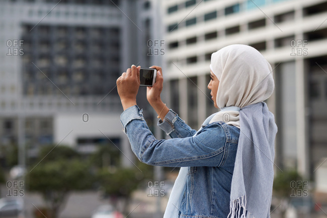 Young muslim woman taking photo using smartphone in city tourist photographing urban travel with mobile phone camera wearing hijab headscarf