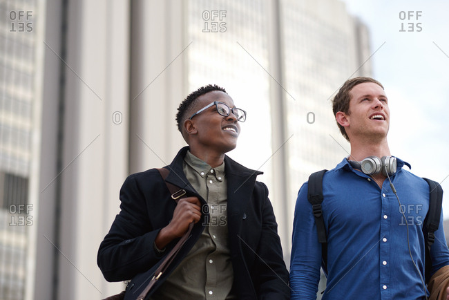 Two young businessmen walking in city best friends commuting after work business students on university campus