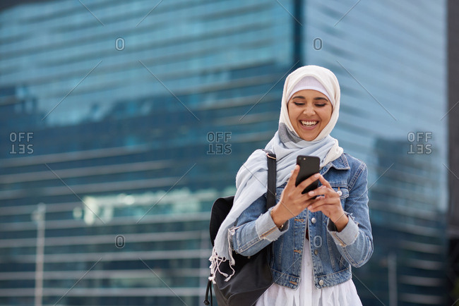 Young muslim woman using smartphone in city texting on mobile phone wearing traditional hijab headscarf