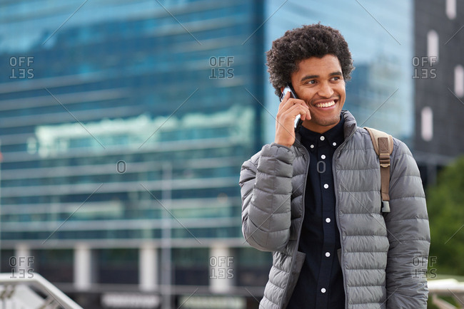 Portrait man using smartphone chatting on mobile phone having conversation in city