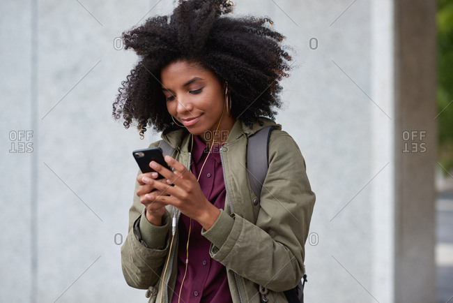 African american woman using smartphone in city wearing earphones listening to music with mobile phone