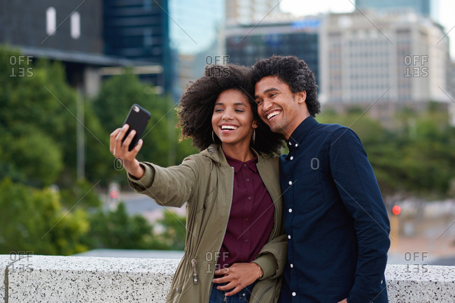 Happy couple taking selfie photos using smartphone in city photographing romantic date together with mobile phone camera