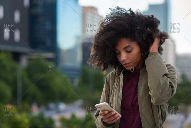 African american woman using smartphone in city texting browsing messages on mobile phone technology