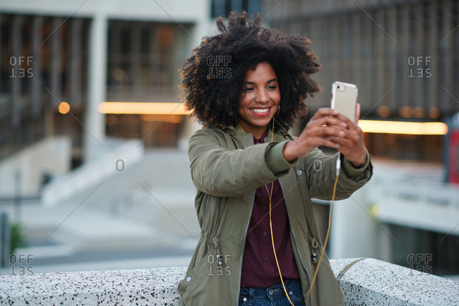 African american woman taking selfie photo using smartphone in city with mobile phone camera