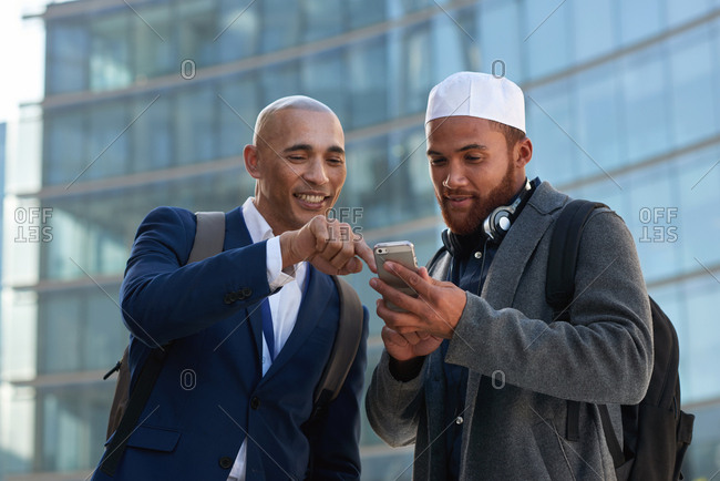 Two businessmen using smartphone businessman showing friend mobile phone in city
