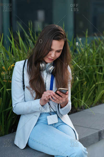 Young business woman using smartphone in city texting on mobile phone browsing online relaxing on lunch break