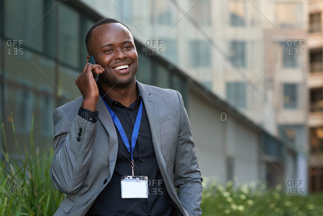 African american businessman using smartphone talking on mobile phone in city