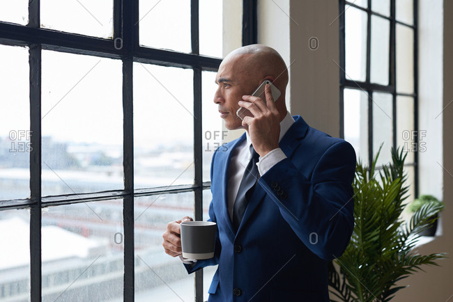 Businessman talking on smartphone looking out window having phone call conversation in office holding coffee