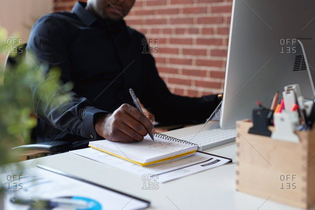 African american businessman writing in notebook journal on desk list of goals in diary making notes